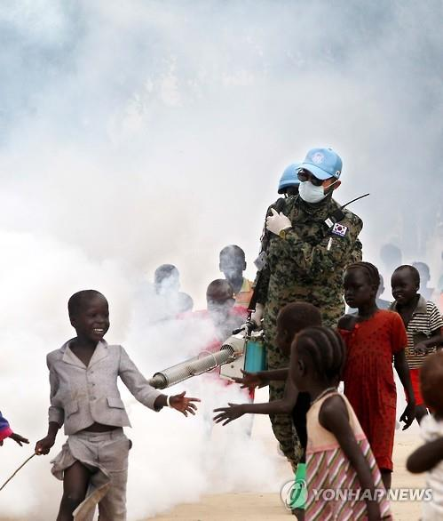 Members of South Korea's Hanbit unit, surrounded by young kids, spray disinfectant at a protection-of-civilians site where about 2,300 war-displaced people are being sheltered in the city of Bor in South Sudan's Jonglei State, on July 9, 2015. (Yonhap)