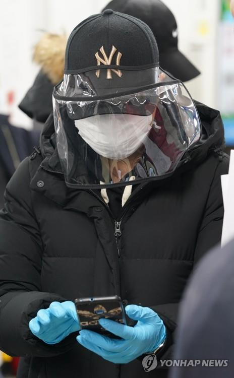 A foreign resident wearing a face mask and a hat with a face shield waits at an immigration office in Seoul on March 6, 2020, to apply for voluntary departure from the country amid concern about the spread of the new coronavirus. (Yonhap)