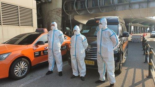 This photo, provided by the Seoul city government, shows taxi drivers in protective gear who have been exclusively transporting passengers from abroad at Incheon International Airport, west of Seoul, since March 31, 2020.