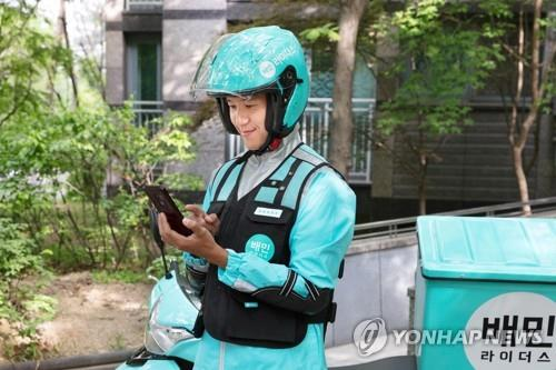 This photo, provided by Woowa Brothers, shows a Baemin deliveryman. (NOT FOR SALE). (Yonhap)