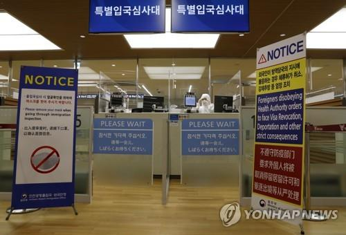 Immigration officials clad in protective gear work at immigration counters exclusively for inbound visitors with symptoms of the new coronavirus at Incheon International Airport, west of Seoul, on April 8, 2020. (Yonhap)