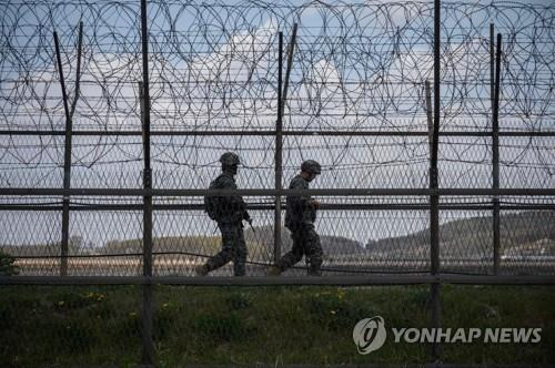 This AFP photo, taken on April 23, 2020, shows South Korean soldiers patrolling along a barbed wire fence in the Demilitarized Zone (DMZ) separating North and South Korea, on the South Korean island of Ganghwa. (Yonhap)