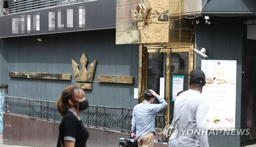 People walk past a dance club in the popular international district of Itaewon in Seoul on May 7, 2020. The club was shut down, as a man in his 20s who tested positive for COVID-19 visited the place on May 1. Some 500 people were reportedly there at that time. (Yonhap)