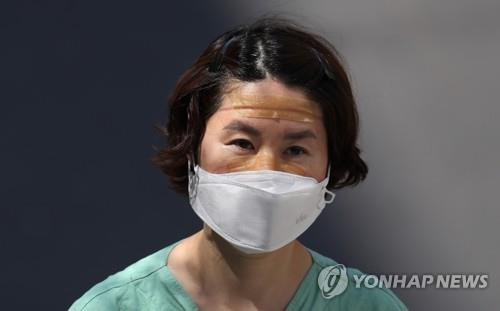 A medical worker looks tired after completing a shift for the service of people infected with the new coronavirus at a hospital in the southeastern city of Daegu, the epicenter of South Korea's COVID-19 virus outbreak, on April 3, 2020. (Yonhap)