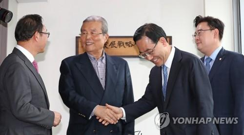 Kim Chong-in (2nd from L) shakes hands with United Future Party floor leader Rep. Joo Ho-young in his office in Seoul on May 22, 2020, after accepting the post as the head of the party's emergency leadership body. (Yonhap)