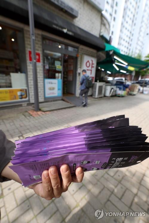 A customer holds a bundle of masks for himself and his family after purchasing them at a drugstore in Gwangju, 329 kilometers south of Seoul, on June 1, 2020. No standing in line was necessary. (Yonhap)