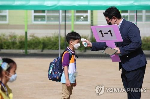 A teacher checks a first grader's temperature at Dongdo Elementary School in Daegu on May 27, 2020. South Korea implemented the second phase of school reopenings the same day for the two lowest grades of elementary school, kindergarten students, middle school seniors and second-year high school students. (Yonhap)