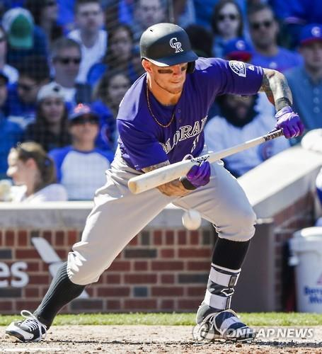 In this EPA file photo from April 17, 2016, Brandon Barnes of the Colorado Rockies attempts a bunt against the Chicago Cubs during their Major League Baseball regular season game at Wrigley Field in Chicago. (Yonhap)