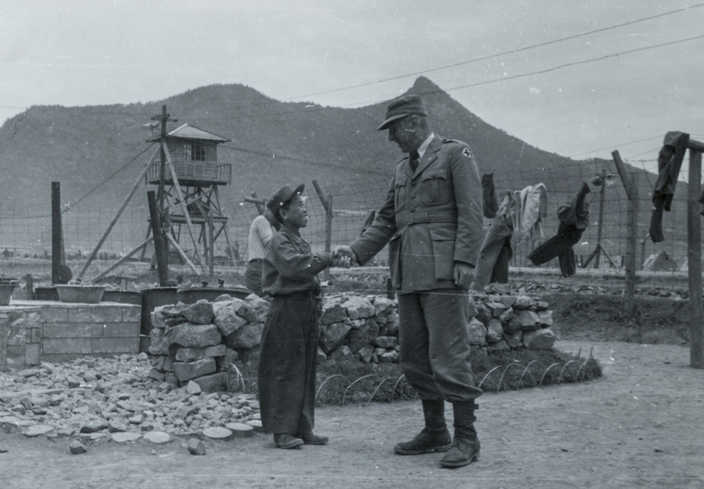 A little boy shakes hands with an ICRC official with a broad smile on his face at a POW camp in Geoje in a photo taken by the ICRC on June 4, 1951. (PHOTO NOT FOR SALE) (Yonhap)