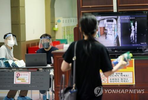 A exam taker has her body temperature checked at a school in the southern city of Gwangju where a national examination for recruitment of entry-level civil servants was held on July 11, 2020. (Yonhap)