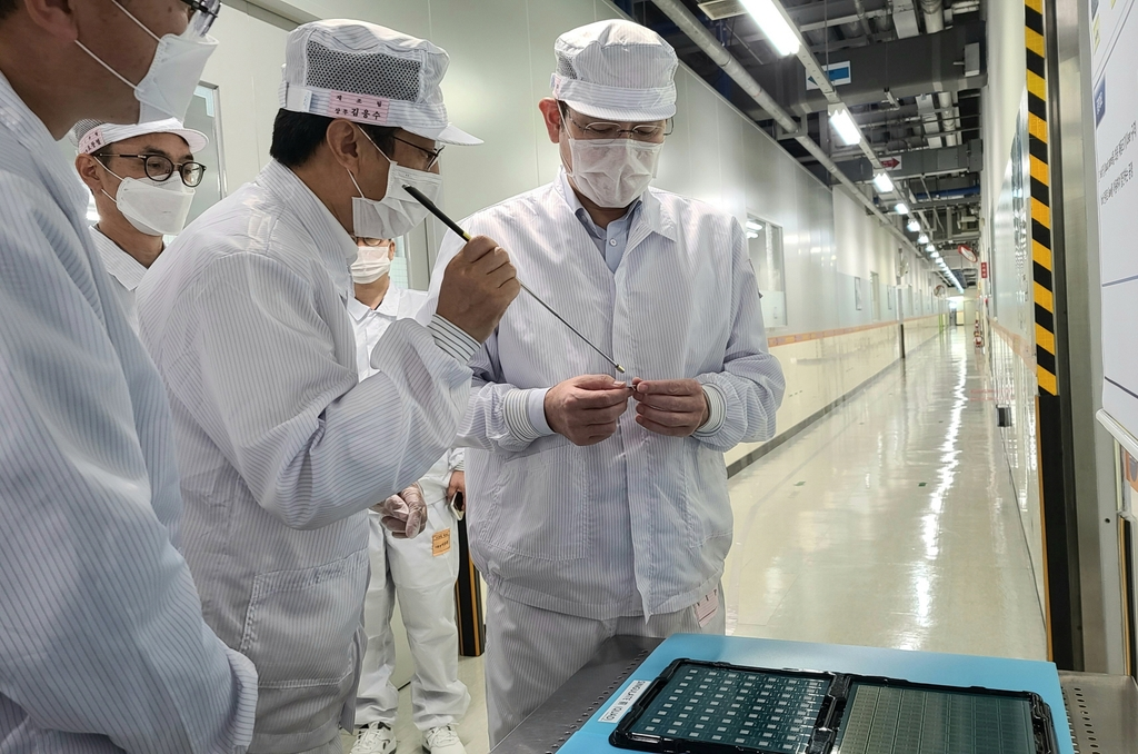 This photo, provided by Samsung Electronics Co. on July 16, 2020, shows Samsung Electronics Vice Chairman Lee Jae-yong (R) looking at Samsung Electro-Mechanics Co.'s package substrate product at the company's plant in Busan. (PHOTO NOT FOR SALE) (Yonhap)
