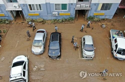 Army soldiers and volunteers engage in restoration work at a flooded apartment complex in Daejeon, central South Korea, on July 31, 2020. (Yonhap)