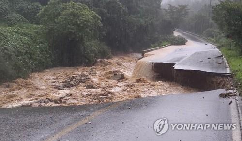 This photo provided by the National Fire Agency shows a collapsed road in Chungju, which left one firefighter missing on Aug. 2, 2020. (PHOTO NOT FOR SALE) (Yonhap)