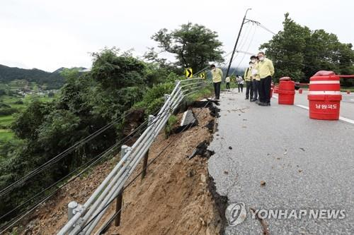 Officials inspect a road partially swept away by torrential rain in Namwon, North Jeolla Province, on Aug. 10, 2020, in this photo provided by the Ministry of Land, Infrastructure and Transport. (PHOTO NOT FOR SALE) (Yonhap)