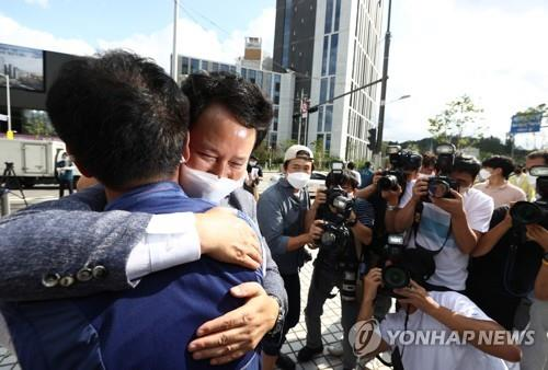 Kwon Jeong-oh, head of the Korean Teachers and Education Workers Union (KTU), celebrates with another union member after hearing a verdict at the Supreme Court in Seoul on Sept. 3, 2020. (Yonhap)
