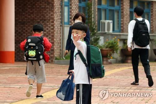 A kid waves to his parent before class in an elementary school in Gwangju on Sept. 14, 2020. (Yonhap)