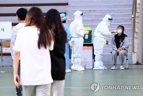 This file photo, taken on Oct. 6, 2020, shows health workers clad in protective gear conducting COVID-19 tests at a middle school in Daejeon after a student tested positive for the novel coronavirus. (Yonhap)