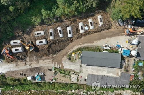 Quarantine workers bury culled pigs near a hog farm in Hwacheon, 120 kilometers east of Seoul, on Oct. 11, 2020, after an additional case of the African swine fever was reported in the region. (Yonhap)