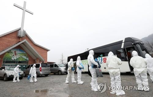 IEM School students and instructors, who tested positive for COVID-19 while attending a winter retreat at a church in Hongcheon, southeast of Seoul, prepare to board a bus bound for a residential treatment center on Jan. 26, 2021. (Yonhap)