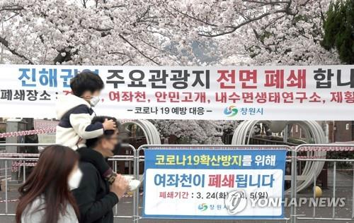 Citizens pass by a banner announcing the cancellation of the Jinhae Gunhangje Festival in Changwon, southeastern South Korea, in this file photo taken on March 29, 2020. (Yonhap)