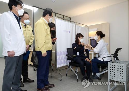 Chung Mi-kyeong (2nd from R), a sanitation worker of the National Medical Center, receives a Pfizer vaccine at the hospital in central Seoul on Feb. 27, 2021, while Prime Minister Chung Sye-kyun (3rd from L) looks on. She became the first South Korean to get the Pfizer product. (Yonhap)