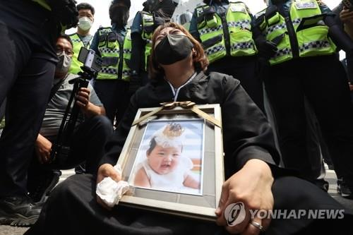 A protestor holds a funeral photo of Jung-in near the Seoul Southern District Court on May 14, 2021. (Yonhap)
