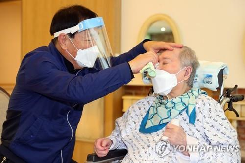 A man wipes away his wife's tears at a nursing home in Gwangju, Gyeonggi Province, on Sept. 20, 2021. The couple met in person for the first time in two months as the government has enforced special quarantine steps for the Chuseok holiday amid the new coronavirus, in this photo provided by the health ministry. (PHOTO NOT FOR SALE) (Yonhap)