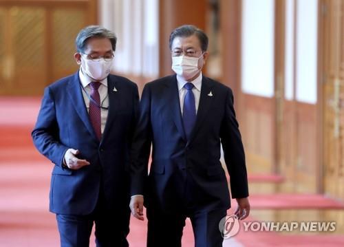 青瓦台で会話する文大統領(右)と盧氏=7日、ソウル(聯合ニュース)