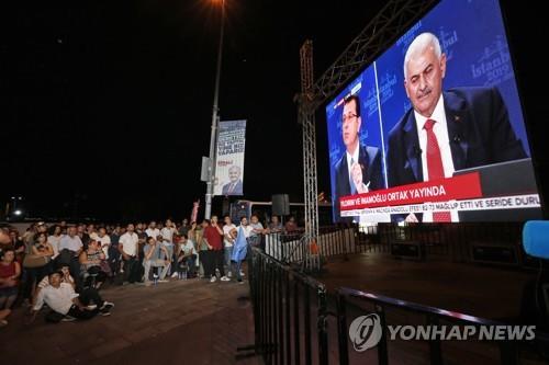 터키 시민들이 현지시간 16일 오후 방영된 이스탄불 시장 재선거 TV토론을 보고 있다. 중계된 화면의 오른쪽이 집권 '정의개발당'(AKP) 비날리 이을드름(63) 후보이고 왼쪽이 제1야당 '공화인민당'(CHP)의 에크렘 이마모을루(49) 후보다. [AP=연합뉴스]