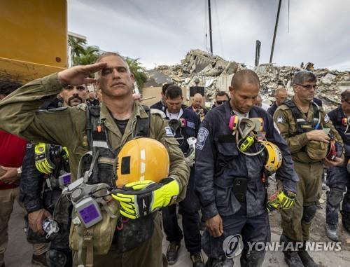 미국 플로리다주 아파트 붕괴 수색현장에서 잠시 일손을 멈추고 묵념을 하는 구조대원들 [마이애미헤럴드/AP=연합뉴스 자료사진]