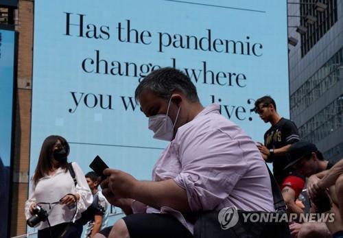 22일(현지시간) 미국 뉴욕의 타임스스퀘어에 마스크를 쓴 사람들이 앉아 있다. [AFP=연합뉴스]