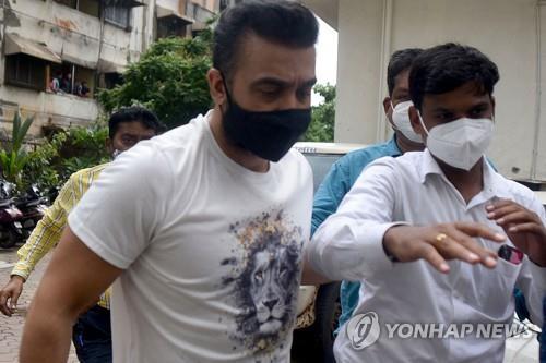 경찰에 체포된 라지 쿤드라(왼쪽). [AFP=연합뉴스]