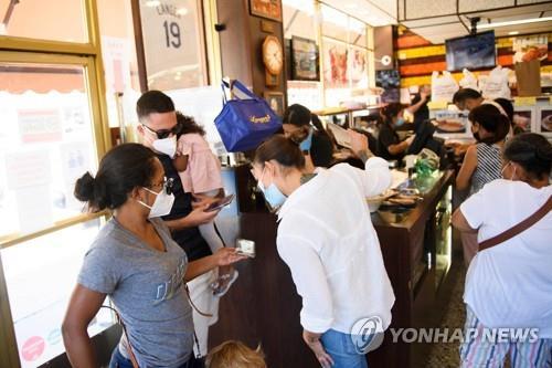 7일(현지시간) 미국 LA의 한 식당에서 직원이 손님들의 디지털 백신 접종 증명서를 확인하고 있다. 이 식당은 실내에서 식사하려는 손님에게 백신 증명서를 제출하도록 했다. [AFP=연합뉴스]