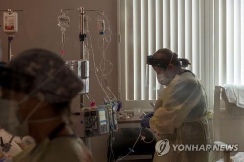 지난달 미 캘리포니아 소노라의 애드벤티스 헬스 병원 중환자실에서 간호사가 코로나19 환자의 상태를 살펴보고 있다. [AFP=연합뉴스]