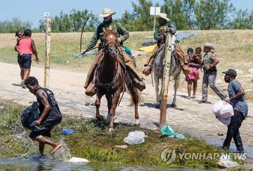 말 고삐를 휘두르는 미 국경순찰대에 쫓기는 아이티 난민들