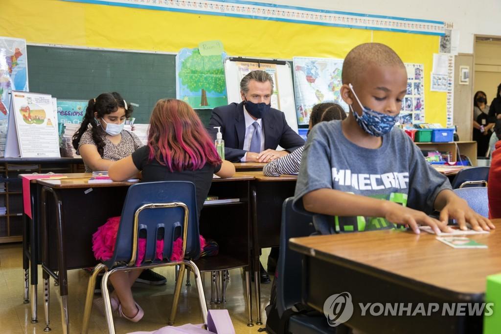 11일(현지시간) 초중고 교직원에 백신접종을 의무화하는 행정명령을 발표한 개빈 뉴섬 캘리포니아 주지사가 칼 B. 먼크 초등학교 2학년 교실에서 수업을 참여하고 있다. [샌프란시스코크로니클/AP=연합뉴스]
