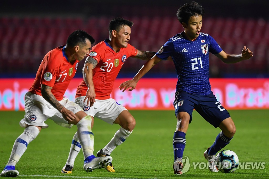 In this AFP photo from June 17, 2019, Takefusa Kubo of Japan (R) is pursued by Charles Aranguiz (C) and Gary Medel of Chile during the teams' Group C match at Copa America at Cicero Pompeu de Toledo Stadium in Sao Paulo. (Yonhap)