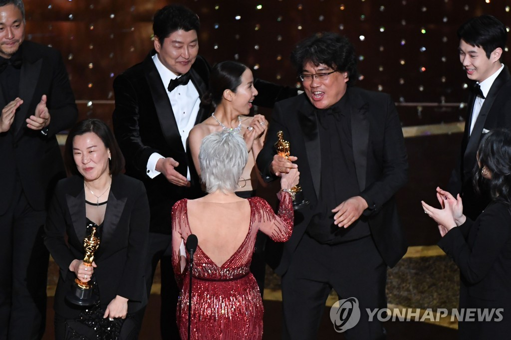 "In this photo released by AFP, ""Parasite"" producers Kwak Sin-ae (L) and Bong Joon-ho (R) accept the best picture award for the film during the 92nd Oscars at the Dolby Theatre in Los Angeles on Feb. 9, 2020. (Yonhap)"