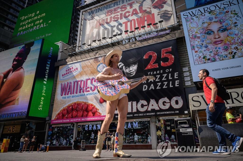 뉴욕시 타임스스퀘어의 광고들 앞에 서 있는 '네이키드 카우보이'