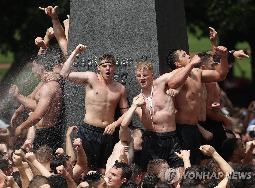 US-NAVAL-ACADEMY-FRESHMAN-CLIMB-GREASED-MONUMENT-IN-ANNUAL-RITE-