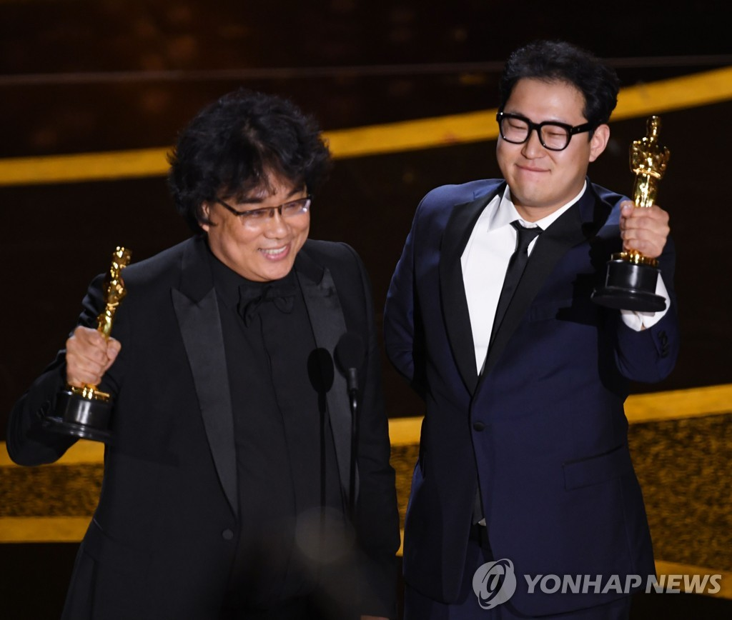 "Bong Joon-ho (L) and Han Jin-won accept the best original screenplay award for ""Parasite"" during the 92nd Oscars at the Dolby Theatre in Los Angeles on Feb. 9 in this photo released by AFP. (Yonhap)"