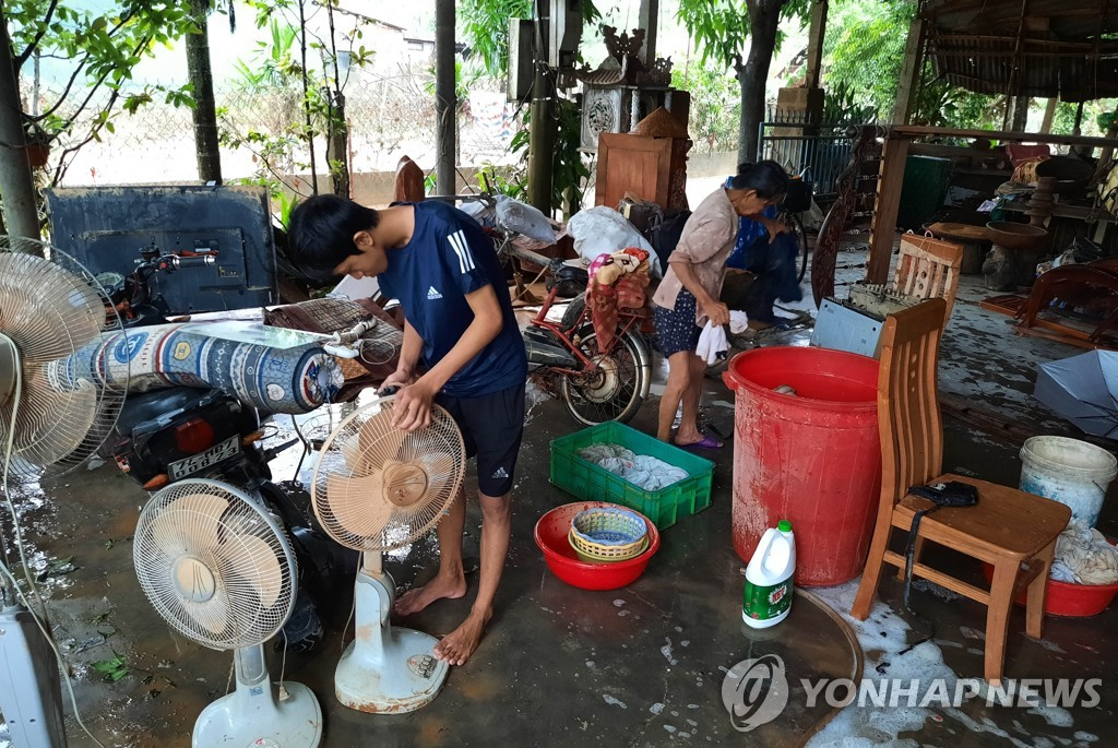 This Xinhua photo shows residents checking their belongings at a local community in Quang Tri Province in central Vietnam on Oct. 20, 2020, after floods caused by heavy downpours that left at least 105 people dead. (Yonhap)