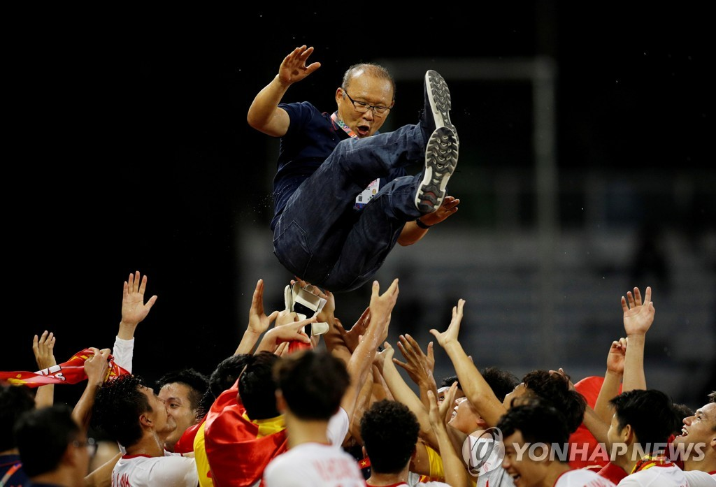In this Reuters photo, members of the Vietnamese men's under-22 national football team toss head coach Park Hang-seo in the air in celebration of their gold medal at the Southeast Asian Games at Rizal Memorial Stadium in Manila on Dec. 10, 2019. (Yonhap)