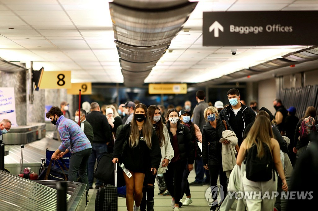 덴버의 공항에서 마스크를 쓰고 수화물을 찾으러 가는 여행객들 [로이터=연합뉴스]