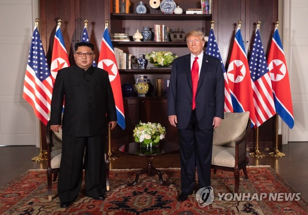 U.S. President Donald Trump (R) poses with North Korean leader Kim Jong-un at the Capella Hotel in Singapore on June 12, 2018, while having a one-on-one summit there, in this photo captured from the Twitter account of White House social media director Dan Scavino. (Yonhap)
