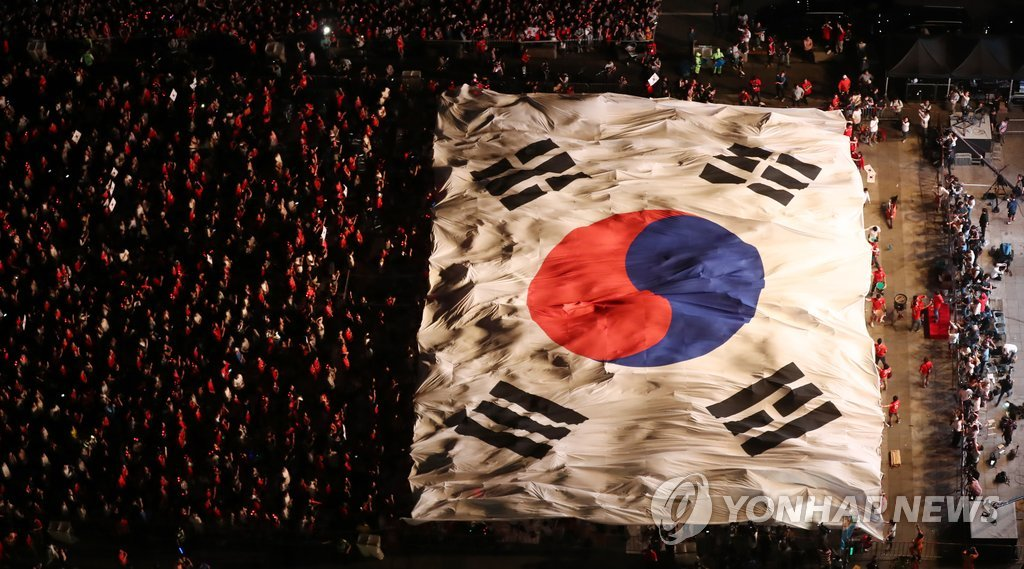 A huge South Korean national flag, the Taegeukki, is held up by football fans gathered at Gwanghwamun Square in central Seoul in this file photo from June 18, 2018, as they cheer for the Korean national team during its World Cup Group F showdown against Sweden. (Yonhap)