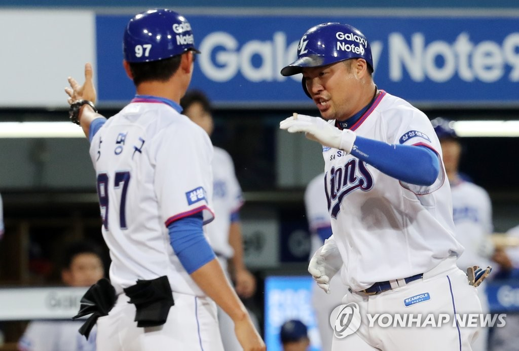 In this file photo from Sept. 6, 2018, Park Han-yi of the Samsung Lions (R) is greeted at the home plate by his first base coach, Kang Myung-gu, after hitting a solo home run against the Doosan Bears in the bottom of the second inning of a Korea Baseball Organization regular season game at Daegu Samsung Lions Park in Daegu, 300 kilometers southeast of Seoul. (Yonhap)