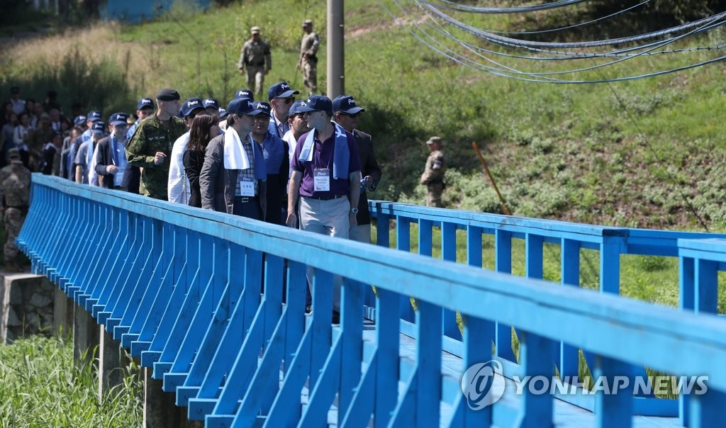 "In this photo provided by the cultre ministry, South Korean Culture Minister Do Jong-whan and foreign diplomats stationed in Seoul walk onto the ""Foot Bridge"" during a visit to the Demilitarized Zone that separates the two Koreas, north of Seoul, on Sep. 7, 2018. The bridge is where South and North Korea's leaders strolled and talked during their summit on April 27. (Yonhap)"