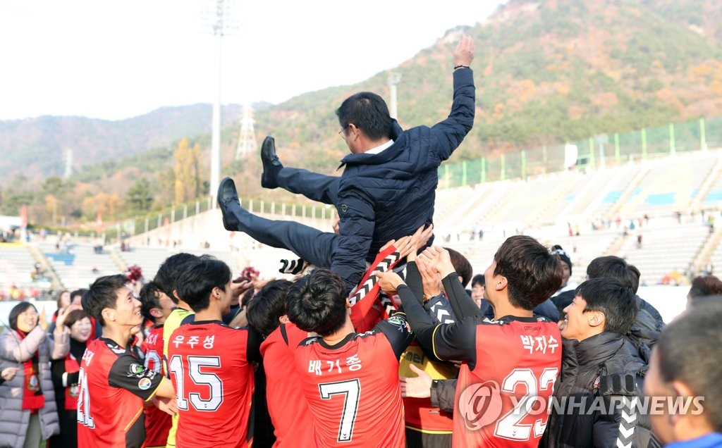 In this file photo taken on Nov. 25, 2018, Gyeongnam FC head coach Kim Jong-boo (C) is tossed in the air after his side clinched a second-place finish in the K League 1 at Changwon Football Center in Changwon. (Yonhap)