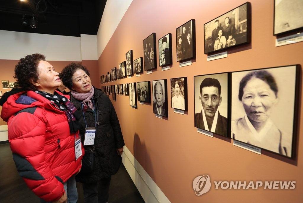 Women view photos at an observatory in the South Korean border city of Paju on Nov. 29, 2018, as they visit an exhibition on records of families separated by the 1950-53 Korean War. (Yonhap)